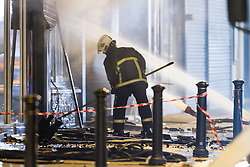 © Licensed to London News Pictures . 13/07/2013 . Manchester , UK . A fireman picks through debris at the scene . A fire fighter is dead and two 15 year old girls are under arrest on suspicion of manslaughter after a blaze in Manchester yesterday (Saturday 13th July) . More than 60 fire fighters tackled a blaze at Paul's Hair World on Oldham Street in Manchester City Centre late in to the night (Saturday 13th July 2013) . Twelve crews from four stations were deployed . Several streets in a block in the city centre are sealed off . Photo credit : Joel Goodman/LNP