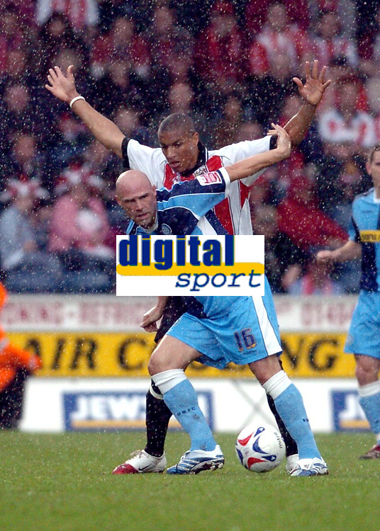 Photo: Leigh Quinnell.<br /> Wycombe Wanderers v Cheltenham Town. Coca Cola League 2, Play off Semi Final. 13/05/2006. Wycombes Tommy Mooney battles with Cheltenhams Gavin Caines in a heavy rain storm.