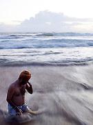 Local man in surf at Papanasham Beach (Beach of Redemption), Varkala, Kerala, India