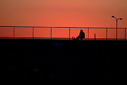 A lone fan sits atop the bleechers next to a football game as the sunsets in the west behind him.