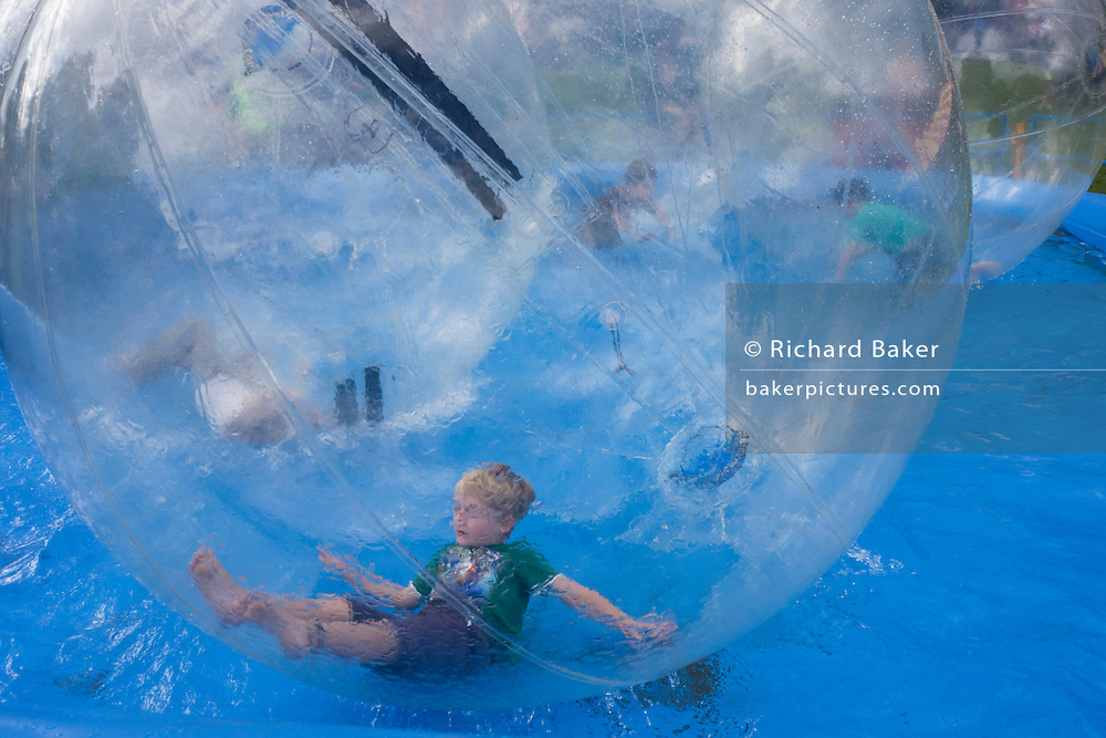 Children roll around the inside of Water Balls at the south London Lambeth Country Fair. A water ball is a large inflatable sphere that allows a person to walk across a water surface. The water ball is similar to a zorb (rolling downhill in an orb, generally made of transparent plastic), but this has only one layer and is designed for water travel rather than downhill rolling. The giant ball is usually two metres in diameter and has a zippered entrance to allow for easy entry and exit. It stores flat and weighs 15 kilograms. The best water balls are constructed from polyvinyl chloride (PVC) 0.6-0.7mm thick. http://en.wikipedia.org/wiki/Water_ball