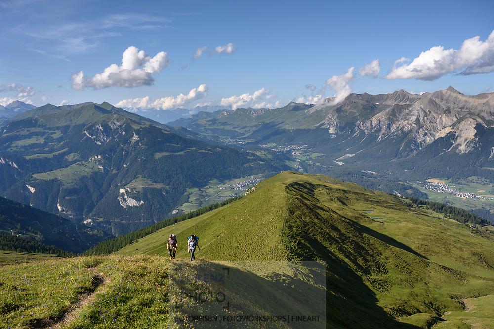 Zwei Wanderer auf einer Wanderung von der Alp da Stierva auf den Curver Pintg mit Blick in Richtung Lenzerheide, Savognin, Parc Ela, Graubünden, Schweiz<br /> <br /> Two hikers on a hike from the Alp da Stierva to the Curver Pintg with a view towards Lenzerheide, Savognin, Parc Ela, Grisons, Switzerland