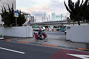 cyclist with two children in Tokyo Shibaura district with the JR rail line in the background