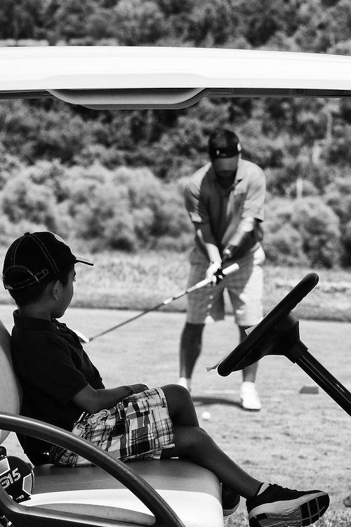 Wounded vetaran Roman Padilla enjoys a game of golf while his son takes some shade in the cart during the Cal Ripken, Sr. Foundation Golf Classic benefit at the Creighton Farms Country Club, VA.