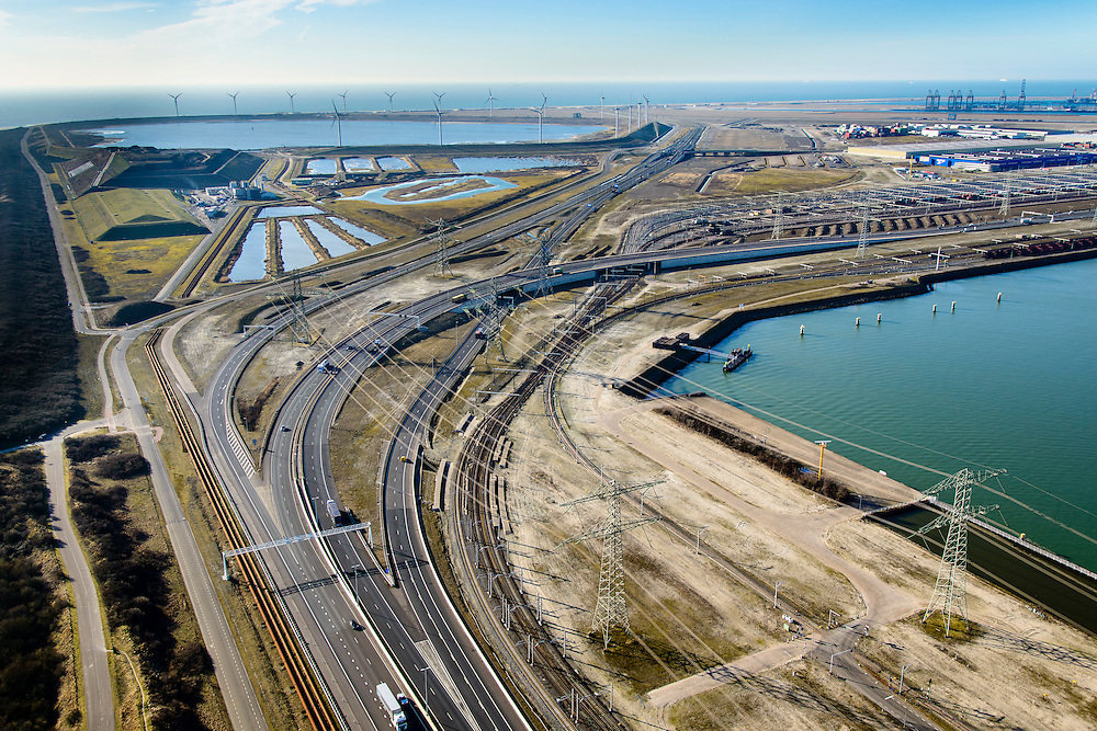 Nederland, Zuid-Holland, Rotterdam, 18-02-2015; Euopaweg buigt af naar de Maasvlakte, Slufter en Tweede Maasvlakte (MV2) in het verschiet. Rechts Emplacement Maasvlakte, Distripark en watrer van de Hartelhaven.<br /> Infrabundel van autosnelweg N15, spoorweg (Betuweroute) en hoogspanningsleidingen. <br /> New and man-made land in the North sea <br /> designate for the Port of Rotterdam.<br /> Infrastructure bundle: motorway, railway (Betuweroute) and power lines.<br /> luchtfoto (toeslag op standard tarieven);<br /> aerial photo (additional fee required);<br /> copyright foto/photo Siebe Swart
