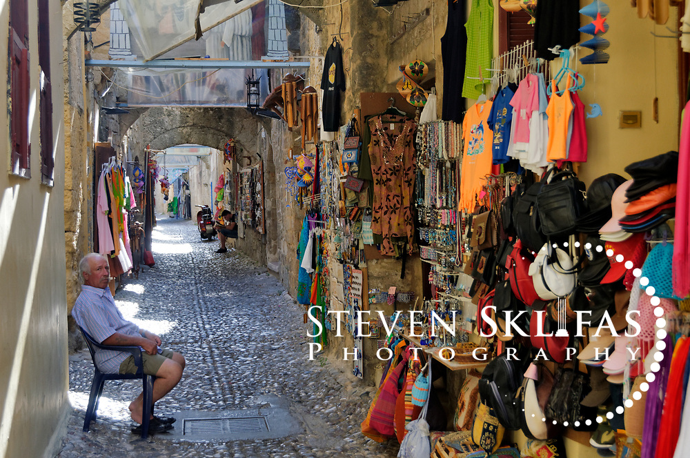Rhodes. Greece. A shopkeeper sitting front of his souvenir shop on a stony alleyway inside the old walled medieval town of Rhodes. The old town is a UNESCO world heritage listed site and the best preserved, oldest and largest living medieval city in Europe. The 4km defensive walls were built by the Knights of St John during the 13th to 15th century to defend Western Europe against the expanding Ottoman Empire. Within the walls are a medieval warren of small alleyways and magnificent historical buildings. The island of Rhodes is the largest of the Dodecanese Island group and one of the most popular Greek Islands.