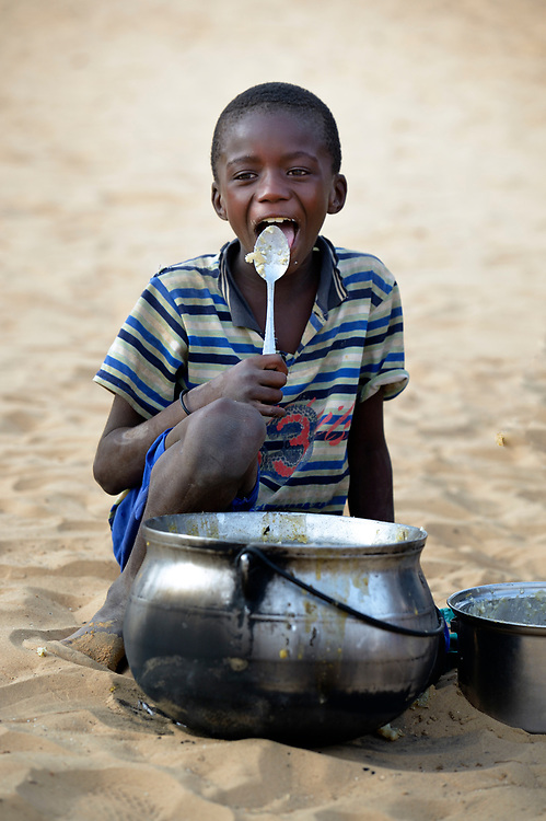 Cisse Al-Husseini, age 9, licks the remaining porridge from a pot in Timbuktu, a city in northern Mali which was seized by Islamist fighters in 2012 and then liberated by French and Malian soldiers in early 2013. The boy belongs to the Bella ethnic group, which has traditionally been exploited by Timbuktu's lighter-skinned groups.