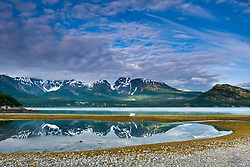 """Red Mountain is reflected in a low tide tidal pool on the beach at Wolf Point on the Muir Inlet in Glacier Bay National Park and Preserve in southeast Alaska. Also pictured at far right is """"The Nunatak, a glaciated knob."""