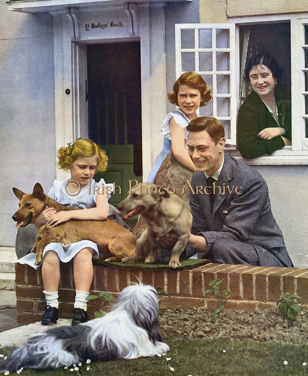 George VI with his daughters and their pet dogs outside Y Bwthyn Bach (The Little House) the gift of the Welsh people to Princess Elizabeth (standing by window). Princes Margaret seated, Queen Elizabeth looks on from inside cottage