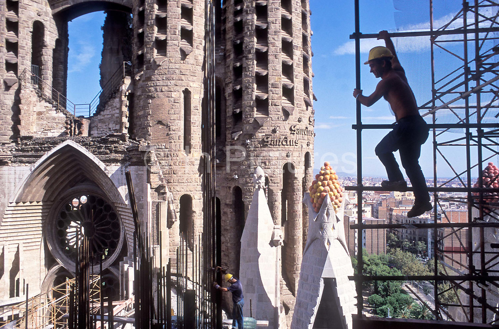 A worker climbs the scaffolding of Gaudi's famed Sagrada familia cathedral. Barcelona, Spain.