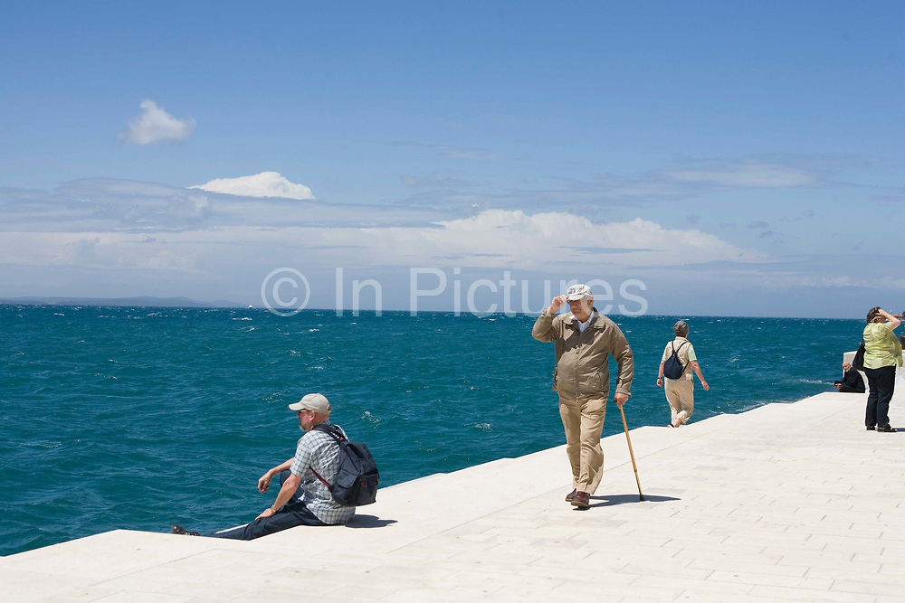 People walking along the front at Zadar to enjoy the sea breeze, Croatia. Part of a story on Croatia's hidden landscape and undiscovered tourism