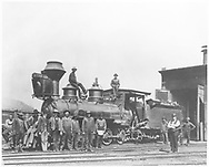 """RGS 2-8-0 #16 in for repairs posing with Durango shop crew.  Notice the damaged cab and tender front from a collision with cars at Durango smelter.<br /> RGS  Durango, CO  Taken by Root, George - 7/1903<br /> In book """"Narrow Gauge Country 1870-1970"""" page 104<br /> Uncropped version of RD155-030 except a lighter print.<br /> Also in """"Silver San Juan"""", p. 111 and """"RGS Story Vol. IX"""", p. 376 (Jacob G. Willson photographer)."""
