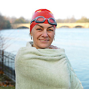 Portrait of a member of the Serpentine Swimming Club wrapped in a green towel, Hyde Park, London, UK. The Serpentine Lake is situated in Hyde Park, London's largest central open space. The Serpentine Swimming Club was formed in 1864 'to promote the healthful habit of bathing in open water throughout the year'.  Its headquarters were beneath an old elm tree on the south side of the lake, a wooden bench for clothing being the only facility.  At this time London was undergoing rapid expansion and Hyde Park was now in the centre of a densely populated built up area and provided a place of relaxation to its urbanised masses. Now, the club has its own (somewhat spartan) changing facilities and members are  permitted by the Royal Parks to swim in the lake any morning before 09:30.  They race every Saturday morning throughout the year, regardless of the weather.