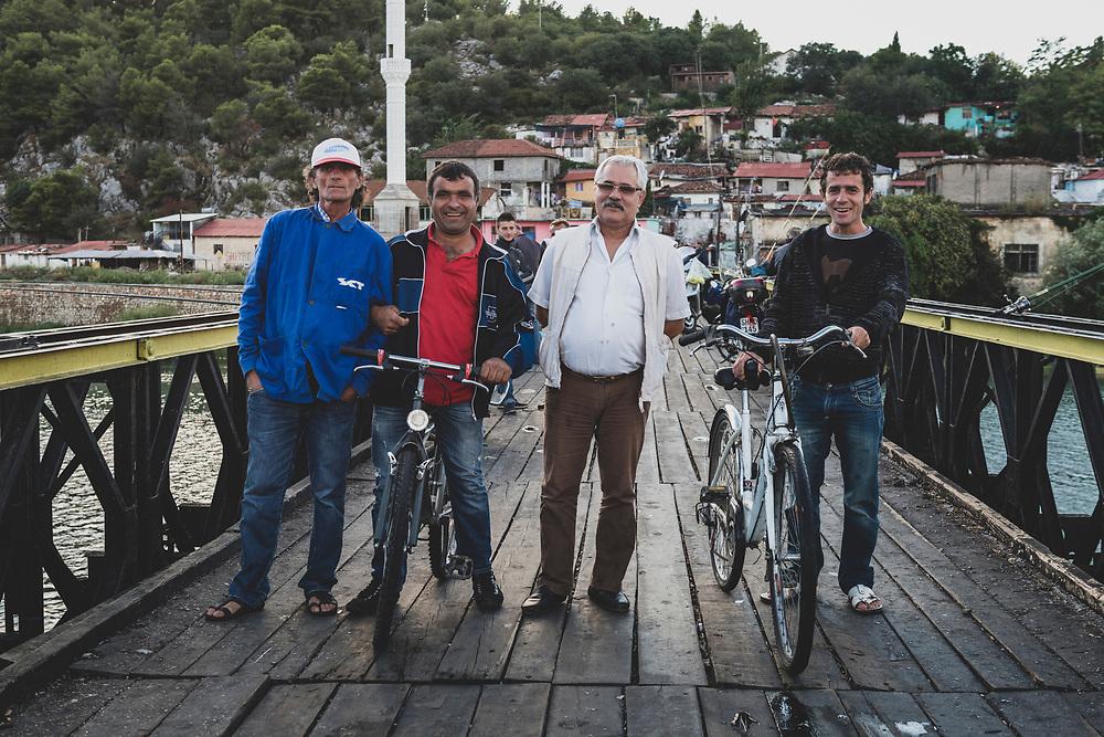Men stop for a picture while crossing The Old Buna Bridge (Ura e Vjetër e Bunës) in Shkodër (Shkodra), Albania. <br /> <br /> (September 2013)