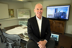 Terrence McGrath, founder of McGrath Properties, poses for a photograph with an artist's rendering of the high-rise building he is pitching to the city of Oakland for construction near the MacArthur BART station, at his offices in Oakland, Calif., Tuesday, April 11, 2017. (Photo by D. Ross Cameron)