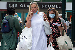 ©Licensed to London News Pictures 24/07/2020     <br /> Bromley, UK. Shoppers coming out of the Glades shopping centre in Bromley High Street, South East London today wearing face masks. A face mask or covering becomes compulsory from today when entering a petrol station, shop, train station, bank, post office or a shopping centre. The new rule is to help in the fight against coronavirus. Photo credit: Grant Falvey/LNP
