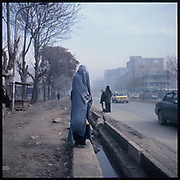 A woman clad in burqa stands on the curb before crossing a street in Kabul.