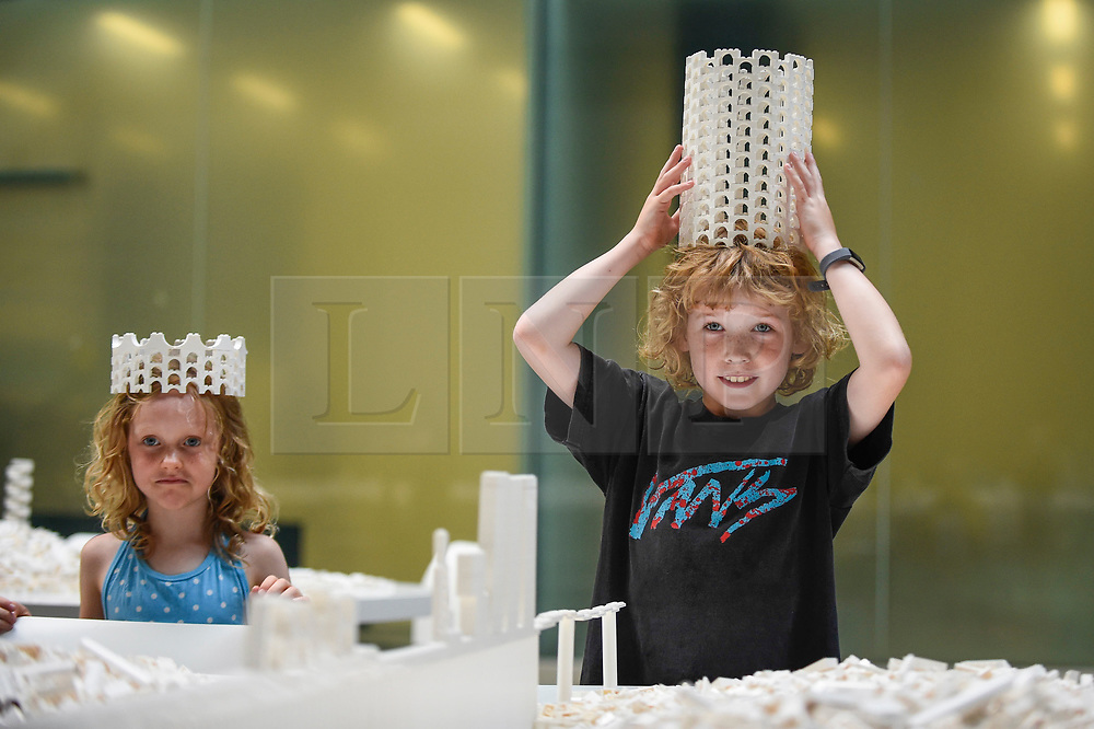 """© Licensed to London News Pictures. 26/07/2019. LONDON, UK. Willow Beal, aged 5 (L), and Hunter Tagholm (R), aged 8, pose with a Lego crown at the preview of """"The cubic structural evolution project"""", 2004, by Olafur Eliasson at Tate Modern.  Exhibited for the first time in the UK, the artwork comprises one tonne of white Lego bricks inspiring visitors to create their own architectural vision for a future city and is on display until 18 August 2019.  The work coincides with the artist's new retrospective exhibition """"In real life"""" at Tate Modern on display to 5 January 2020. (Parental permission to photograph obtained). Photo credit: Stephen Chung/LNP"""