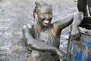 Israel, Dead Sea, tourist covers herself in therapeutic mud in order to benefit from claimed skin care properties of this mud. (Model Release Available)