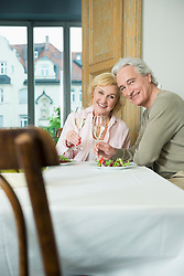 Portrait of mature couple sitting at table with sprinkling wine, smiling