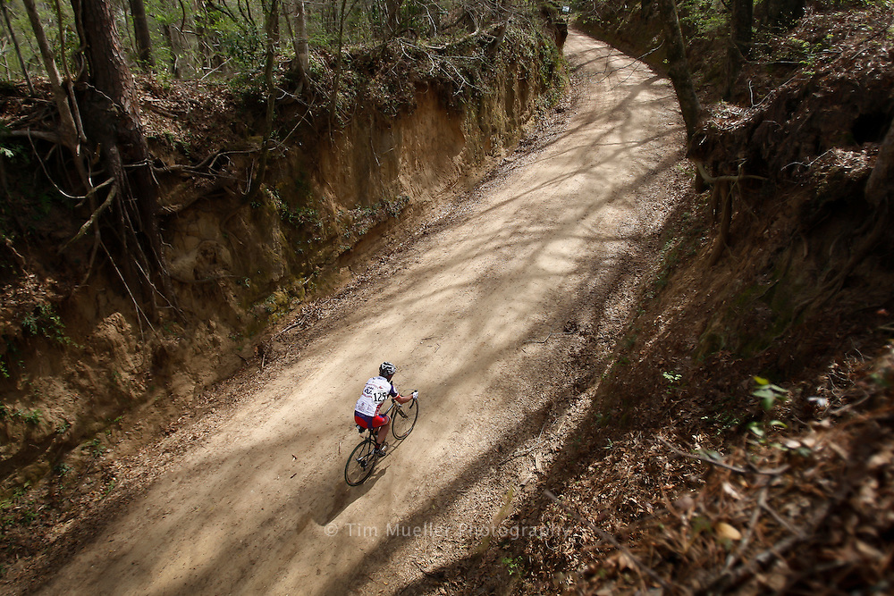 A lone competitor climbs up a steep hill called Big Bertha on Old Tunica Road during Rouge Roubaix XI. The 100 mile road race begins in St. Francisville, La. and travels north through the back roads of West Feliciana Parish and Wilkinson County, Mississippi.