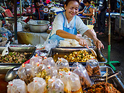 20 JUNE 2018 - BANGKOK, THAILAND: A food vender at Makkasan Market, a small local market in central Bangkok, prepares take away orders of curries in plastic bags. Officials in Thailand are wrestling with Thais use of plastic bags. The issue became a public one in early June when a whale in Thai waters died after ingesting 18 pounds of plastic. In a recent report, Ocean Conservancy claimed that Thailand, China, Indonesia, the Philippines, and Vietnam were responsible for as much as 60 percent of the plastic waste in the world's oceans.    PHOTO BY JACK KURTZ