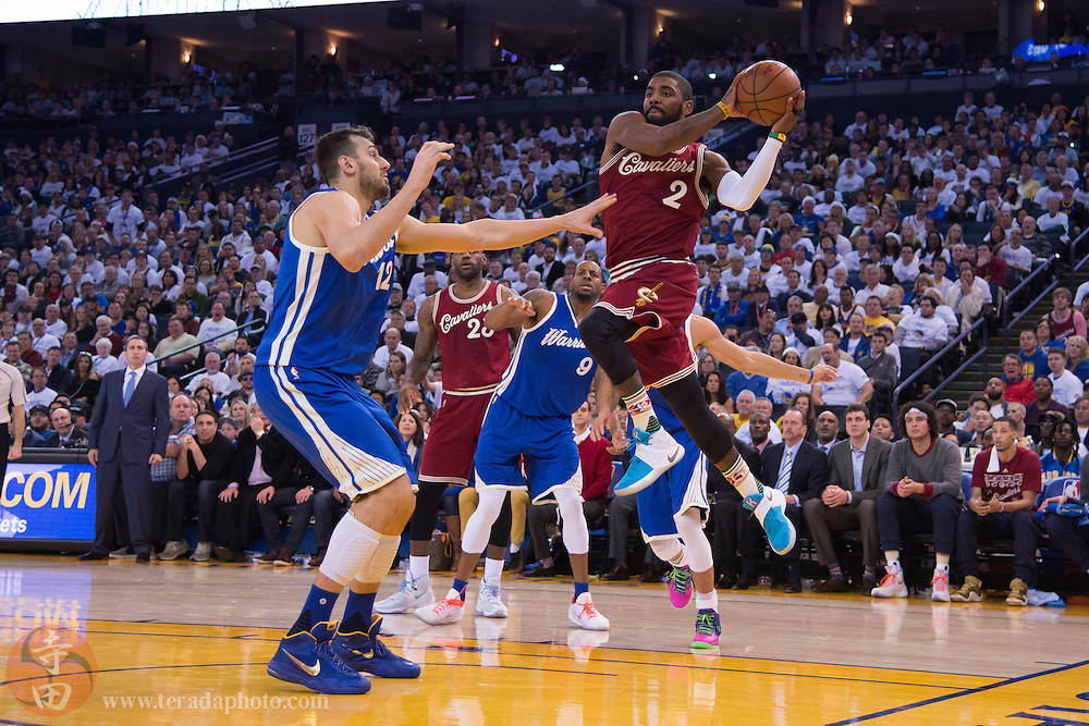December 25, 2015; Oakland, CA, USA; Cleveland Cavaliers guard Kyrie Irving (2) passes the basketball against Golden State Warriors center Andrew Bogut (12) during the second quarter in a NBA basketball game on Christmas at Oracle Arena. The Warriors defeated the Cavaliers 89-83.