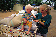 Alet van der Walt and her two-year-old son, Walt, Afrikaaners, carting cleaned, salted, cooked, and dried mopane worms back to South Africa where they will be sold to wholesalers; Walt helps himself to a personal snack of the commodity along the return trip. Botswana. Dried mopane worms have three times the protein content of beef and can be stored for many months. Eaten dry the worms are hard, crispy, and woody tasting. In your mouth, they taste like salty sawdust. (Man Eating Bugs page 131 Top)
