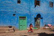 A local girl in red runs past a blue painted house in a village near Medinet Habu on the West Bank of Luxor, Nile Valley, Egypt. This scene is typical of the quiet pace of rural everyday life, far away from the chaotic capital, Cairo whose government controls the policies that affect the people of small villages.