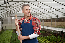 Smiling man in greenhouse