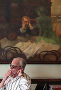 """Gast im berühmten Kaffeehaus SLAVIA in der Prager Innenstadt. Im Hintergrund das Gemälde """"Der Absinthtrinker"""" von Maler Viktor Oliva.<br /> <br /> Visitor at the famous Café Slavia in the city centre of Prague. In the back a painting by Viktor Oliva with the title Absinth drinker."""