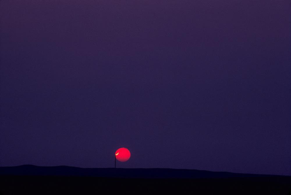 gas burn-off, setting sun