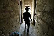 A man walks through his home as he prepares to eat some lunch.  The mountain people of Haiti have built their homes themselves mostly from sticks covered in plaster.  This gentlemans home reflects his higher status because of its block construction.  He has goats that he sells.