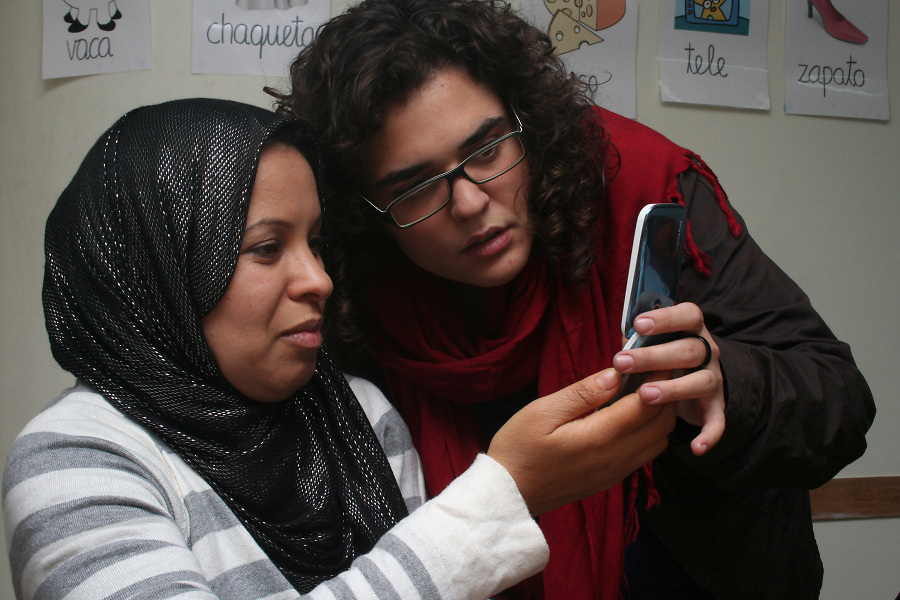 Xenia (Catalonia, 22), a student in social education, helps a young Morrocan woman to write a text on her mobil phone.