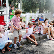 From Left, Darden Shuman, 9, of Charleston, Nolan Shuman, 7, of Charleston, Anna Davis, 7, of Charleston, react as a BJWSA's water truck passes by during the Water Festival Grand Parade. Meanwhile, William Davis, 4, of Charleston, center, seeks cover behind Chilton Grace Simmons , of Beaufort, right, on July 26, 2014.  The Shuman family and Davis families are visiting family in Beaufort and cheering on Beaufort Academy.