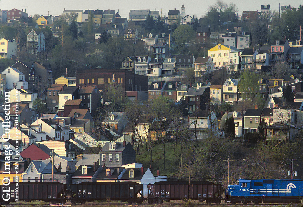 Houses of the South Side Slopes aka Southside Slopes neighborhood of Pittsburgh crowd together on steep hill sloping towards the Monongahela River. A freight train with hopper cars of coal passes. The area was first settled by German immigrant workers for the mills in the 19th century and became most ethnic East European in the 20th century.