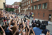 London, UK. Tuesday 23rd July 2013. Kate Middleton and Prince William, The Duke and Duchess of Cambridge, step outside St Mary's Hospital to show their royal baby boy off to the awaiting public and press, the first view following the birth. The scene is one packed with media and cameras, people holding up smartphones.
