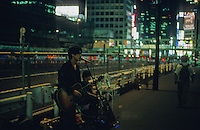 An undiscovered musician performs outside Shinjuku Station south exit, Tokyo.