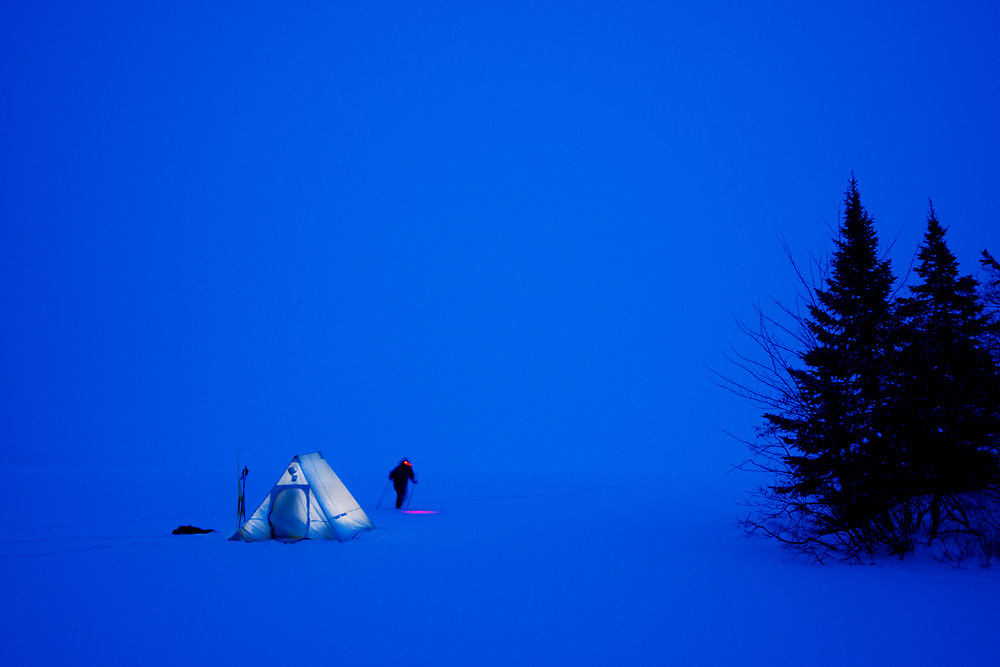 A cross country skier returns to the warmth of a wilderness tent in Minnesota's Superior National Forest.