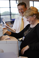 Work colleagues at the photocopier at NHS Octavia House,