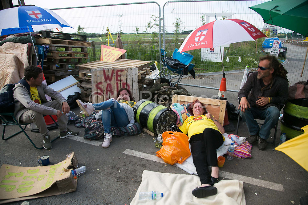 12 local activists locked themselves in specially made arm tubes to block the entrance to Quadrillas drill site in New Preston Road, July 03 2017, Lancashire, United Kingdom. Alana McCulloughv and Michele Martinr still in their lock-ons. The 13 activists included 3 councillors; Julie Brickles, Miranda Cox and Gina Dowding and Nick Danby, Martin Porter, Jeanette Porter,  Michelle Martin, Louise Robinson, Alana McCullough, Nick Sheldrick, Cath Robinson, Barbara Cookson, Dan Huxley-Blyth. The blockade is a repsonse to the emmidiate drilling for shale gas, fracking, by the fracking company Quadrilla. Lancashire voted against permitting fracking but was over ruled by the conservative central Government. All the activists have been active in the struggle against fracking for years but this is their first direct action of peacefull protesting. Fracking is a highly contested way of extracting gas, it is risky to extract and damaging to the environment and is banned in parts of Europe . Lancashire has in the past experienced earth quakes blamed on fracking.
