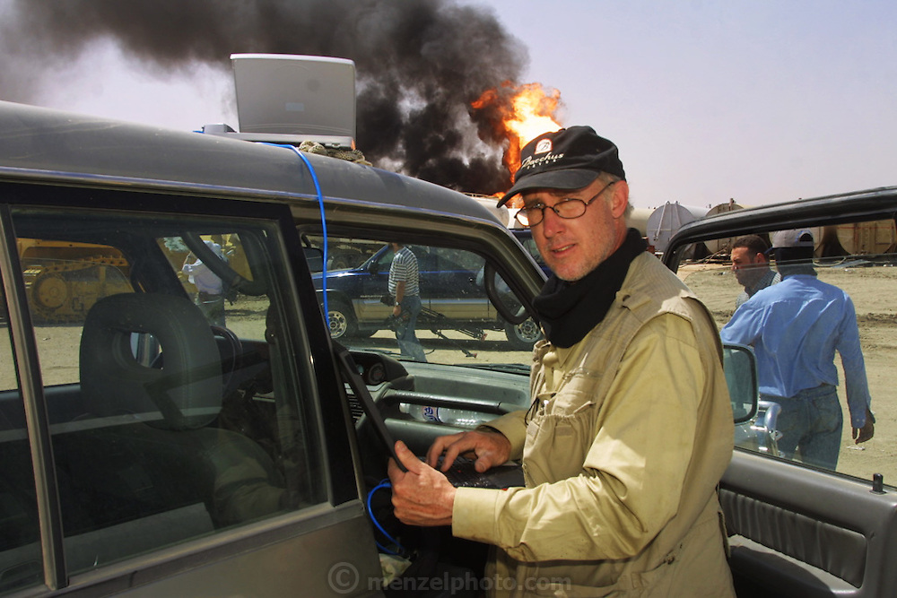 Peter Menzel sending digital images via satellite modem near an oil well in Iraq's Rumaila Oil Field, in southern Iraq. The wells were set on fire with explosives placed by retreating Iraqi troops when the US and UK invasion began. Seven or eight wells were set ablaze but at least one other was detonated but did not ignite. The Rumaila field is one of Iraq's biggest oil fields with five billion barrels in reserve. Many of the wells are 10,000 feet deep and produce huge volumes of oil and gas under tremendous pressure, which makes capping them very difficult and dangerous. Rumaila is also spelled Rumeilah.