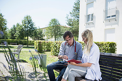 Doctor and nurse working on a bench in the garden with digital tablet and notes, Bavaria, Germany, Europe