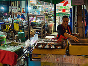 24 FEBRUARY 2016 - BANGKOK, THAILAND: Food and coffee vendors on the sidewalk in front of a 7/11 at Pak Khlong Talat in Bangkok. Bangkok government officials announced this week that vendors in Pak Khlong Talat, Bangkok's well known flower market, don't have to move out on February 28. City officials are trying to clear Bangkok's congested sidewalks and they've cracked down on sidewalk vendors. Several popular sidewalk markets have been closed in recent months and the sidewalk vendors at the flower market had been told they would be evicted at the end of the month but after meeting with vendors and other stake holders city officials relented and said vendors could remain but under stricter guidelines regarding sales hours. The flower market is one of the best known markets in Bangkok and has become a popular tourist destination.        PHOTO BY JACK KURTZ