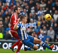 Middlesbrough FC striker Enrique Garcia Kike & Brighton defender Uwe Huenemeier compete for possession during the Sky Bet Championship match between Brighton and Hove Albion and Middlesbrough at the American Express Community Stadium, Brighton and Hove, England on 19 December 2015. Photo by Bennett Dean.
