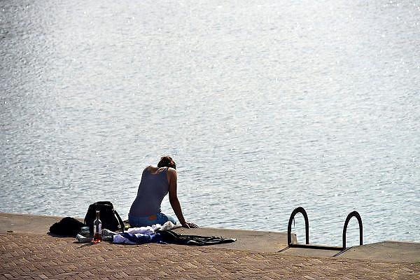 Nederland, Arnhem, 13-3-2014Een jonge vrouw zit op deze mooie en warme voorjaarsdag op de rand van de kade langs de rivier de Rijn, de Rijnkade in de zon. Ze heeft een fles wijn en hapjes bij zich om een buiten, openlucht, lunch, picknick te houden.Foto: Flip Franssen/Hollandse Hoogte