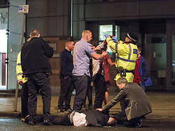 © Licensed to London News Pictures . 21/12/2013 . Manchester , UK . A man lies in the road and another has a bleeding arm following a fight on the city's Charlotte Street . Christmas revellers out in the rain in Manchester on Mad Friday , the last Friday night before Christmas which is typically one of the busiest nights of the year for police and ambulance crews . Photo credit : Joel Goodman/LNP