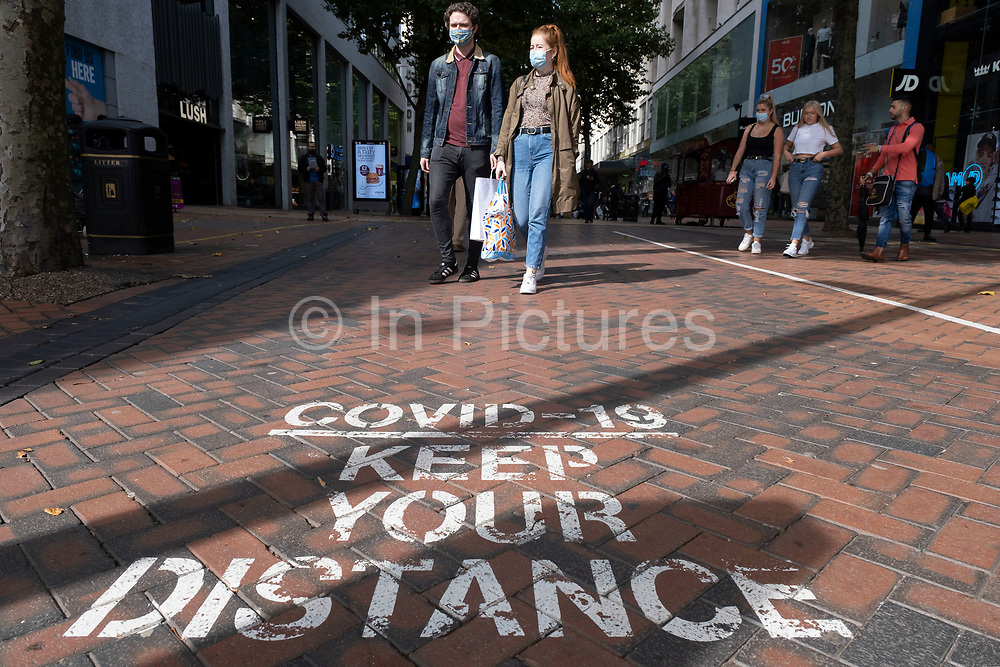 As numbers of Covid-19 cases in Birmingham have dramatically risen in the past week, increased lockdown measures have been announced for Birmingham and other areas of the West Midlands,  people out in the shopping district wearing face masks pass a social distancing sign on the pavement of New Street in the city centre on 12th September 2020 in Birmingham, United Kingdom. With the rule of six also being implemented the Birmingham area has now be escalated to an area of national intervention, with a ban on people socialising with people outside their own household, unless they are from the same support bubble.