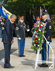 United States President Barack Obama bows his head in respect after laying a wreath during a ceremony at the Tomb of the Unknown Soldier at Arlington National Cemetery in Arlington, Virginia on Veteran's Day, Friday, November 11, 2016. Credit: Ron Sachs / Pool via CNP