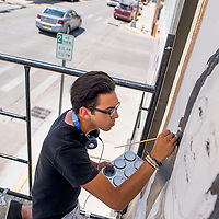 060315       Cable Hoover<br /> <br /> Greg Ballenger paints a portrait of Marine Corps veteran Sheila Silva on the wall of Art123 Gallery in downtown Gallup Wednesday. Ballinger said he intends to complete six more veteran portraits in the downtown area by the end of the summer.